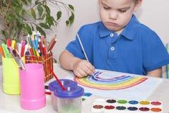 Το αγόρι σύρει τα χρώματα στοκ φωτογραφία
