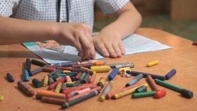 Το αγόρι σύρει τις εικόνες χρησιμοποιώντας τις κιμωλίες και τα μολύβια χρώματος απόθεμα βίντεο