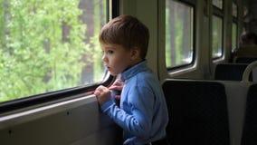 Το αγόρι ταξιδεύει με το τραίνο και φαίνεται έξω το παράθυρο, προσέχοντας τα κινούμενα αντικείμενα έξω από το παράθυρο Ταξίδι με απόθεμα βίντεο