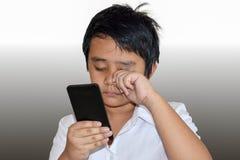 Το αγόρι της Ασίας εξετάζει κινητό και αισθάνεται τον πόνο ματιών Στοκ φωτογραφία με δικαίωμα ελεύθερης χρήσης
