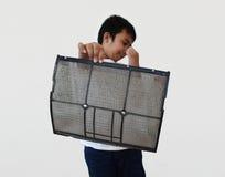 Το αγόρι της Ασίας παρουσιάζει σκόνη φίλτρων αέρα Στοκ Εικόνα