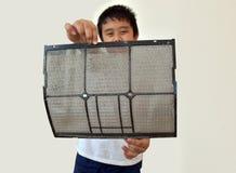 Το αγόρι της Ασίας παρουσιάζει ότι το φίλτρο κλιματιστικών μηχανημάτων έχει τη σκόνη Στοκ Εικόνες