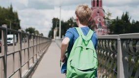 Το αγόρι τρέχει γρήγορα πέρα από τη γέφυρα πέρα από τον ποταμό Δροσεροί δυναμικοί πυροβολισμοί Αθλητικός τρόπος ζωής απόθεμα βίντεο