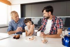 Το αγόρι τρώει ένα κέικ και εξετάζει τον πατέρα του Πίσω από το αγόρι είναι ο παππούς του Πίνουν το τσάι Στοκ Εικόνες