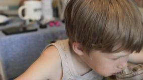 Το αγόρι τρώει ένα σάντουιτς, και τα ποτά Το αγόρι έχει το πρόγευμα απόθεμα βίντεο