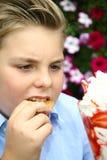 Το αγόρι τρώει το παγωτό, ανθίζει στο υπόβαθρο Στοκ εικόνα με δικαίωμα ελεύθερης χρήσης