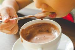 Το αγόρι τρώει την καυτή σοκολάτα Στοκ εικόνες με δικαίωμα ελεύθερης χρήσης
