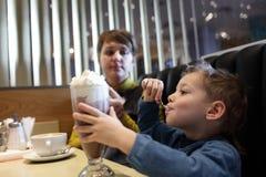 Το αγόρι τρώει τον αφρό του milkshake Στοκ φωτογραφία με δικαίωμα ελεύθερης χρήσης