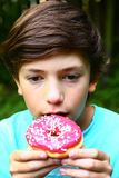 Το αγόρι τρώει doughnut με τη ρόδινη φράουλα Στοκ Φωτογραφία