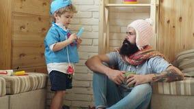 Το αγόρι υπό μορφή γιατρού κάνει ένα τσίμπημα σε ένα γενειοφόρο άτομο Είναι πολύ σημαντικό Γοητευτικό μικρό παιδί σε μια εσθήτα ν φιλμ μικρού μήκους