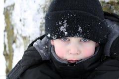 το αγόρι φαίνεται διαπεραστικό χιόνι Στοκ Φωτογραφίες