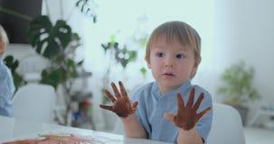 Το αγόρι φεύγει handprints σε χαρτί με τη βοήθεια ενός τραντάγματος Δάχτυλα σχεδίων με τα χρώματα pomuschiyu Ανάπτυξη φιλμ μικρού μήκους