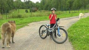 Το αγόρι φορά ένα κράνος κάθεται σε ένα ποδήλατο και διώχνει απόθεμα βίντεο