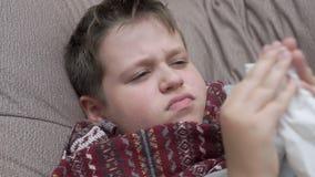 Το αγόρι φυσά τη μύτη του στις πετσέτες εγγράφου Έχει ένα κρύο απόθεμα βίντεο