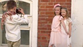 Το αγόρι φωτογραφίζει τις αδελφές στο παλαιό κτήριο τούβλου Τα όμορφα παιδιά σε έναν αναδρομικό στα ενδύματα περνούν καλά επάνω φιλμ μικρού μήκους