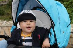 Το αγόρι χαλάρωσε στο μπλε stoller Στοκ Φωτογραφίες