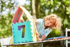 Το αγόρι χτίζει ένα μικροσκοπικό σπίτι από τα κομμάτια γρίφων στοκ φωτογραφία με δικαίωμα ελεύθερης χρήσης