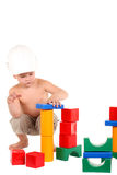 το αγόρι χτίζει τα μικρά παιχνίδια σπιτιών Στοκ Φωτογραφίες