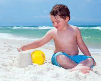 το αγόρι χτίζει τις νεολαίες άμμου κάστρων Στοκ Φωτογραφίες