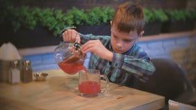 Το αγόρι χύνει κάποιο τσάι των βακκίνιων από teapot στο φλυτζάνι φιλμ μικρού μήκους