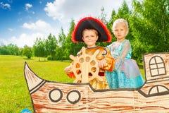 Το αγόρι ως πειρατής κρατά το κορίτσι τιμονιών και πριγκηπισσών Στοκ εικόνα με δικαίωμα ελεύθερης χρήσης
