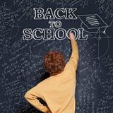 Το αγόρι Сhild γράφει στον πίνακα με την κιμωλία πίσω στο σχολείο στοκ φωτογραφίες