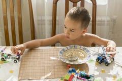 Το αγόρι 4years τρώει το κουάκερ Children& x27 πίνακας του s Η έννοια του child& x27 ανεξαρτησία του s ευτυχής κατανάλωση μικρών  στοκ φωτογραφία με δικαίωμα ελεύθερης χρήσης