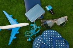 το αεροπλάνο, οι πτώσεις κτυπήματος, το διαβατήριο, λίγη βαλίτσα, τα γυαλιά ηλίου και το καρφί γυαλίζουν στη χλόη Στοκ Εικόνα