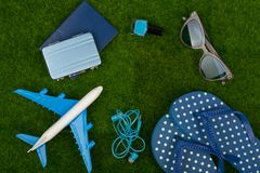 το αεροπλάνο, οι πτώσεις κτυπήματος, το διαβατήριο, λίγη βαλίτσα, τα γυαλιά ηλίου και το καρφί γυαλίζουν στη χλόη Στοκ φωτογραφία με δικαίωμα ελεύθερης χρήσης