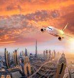 Το αεροπλάνο πετά πέρα από το Ντουμπάι ενάντια στο ζωηρόχρωμο ηλιοβασίλεμα στα Ηνωμένα Αραβικά Εμιράτα Στοκ φωτογραφίες με δικαίωμα ελεύθερης χρήσης
