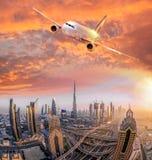 Το αεροπλάνο πετά πέρα από το Ντουμπάι ενάντια στο ζωηρόχρωμο ηλιοβασίλεμα στα Ηνωμένα Αραβικά Εμιράτα Στοκ εικόνα με δικαίωμα ελεύθερης χρήσης
