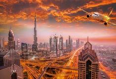 Το αεροπλάνο πετά πέρα από το Ντουμπάι ενάντια στο ζωηρόχρωμο ηλιοβασίλεμα στα Ηνωμένα Αραβικά Εμιράτα Στοκ Φωτογραφίες