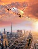 Το αεροπλάνο πετά πέρα από το Ντουμπάι ενάντια στο ζωηρόχρωμο ηλιοβασίλεμα στα Ηνωμένα Αραβικά Εμιράτα Στοκ Φωτογραφία