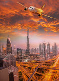 Το αεροπλάνο πετά πέρα από το Ντουμπάι ενάντια στο ζωηρόχρωμο ηλιοβασίλεμα στα Ηνωμένα Αραβικά Εμιράτα Στοκ Εικόνες