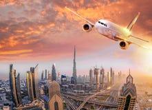 Το αεροπλάνο πετά πέρα από το Ντουμπάι ενάντια στο ζωηρόχρωμο ηλιοβασίλεμα στα Ηνωμένα Αραβικά Εμιράτα Στοκ φωτογραφία με δικαίωμα ελεύθερης χρήσης