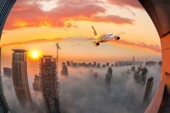 Το αεροπλάνο πετά πέρα από το Ντουμπάι ενάντια στο ζωηρόχρωμο ηλιοβασίλεμα στα Ηνωμένα Αραβικά Εμιράτα Στοκ εικόνες με δικαίωμα ελεύθερης χρήσης
