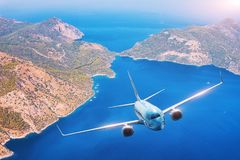 Το αεροπλάνο πετά πέρα από τα νησιά και την ακτή στο ηλιοβασίλεμα το καλοκαίρι Στοκ εικόνα με δικαίωμα ελεύθερης χρήσης