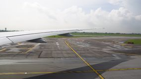 Το αεροπλάνο που μετακινείται με ταξί στο διάδρομο άποψη του φτερού από το παράθυρο αεροπλάνων φιλμ μικρού μήκους