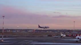 Το αεροπλάνο προσγειώνεται Μεγάλος αριθμός αεροσκαφών που σταθμεύουν Βράδυ Πορφυρά πορτοκαλιά σύννεφα φιλμ μικρού μήκους