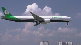 Το αεροπλάνο Boeing 777 του αέρα της Eva που πετά μέσω του ουρανού σύννεφων προετοιμάζεται στην προσγείωση απόθεμα βίντεο