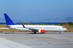 Το αεροπλάνο μετακινούταν με ταξί για την απογείωση στο υπόβαθρο της θάλασσας και των βουνών, Ελλάδα Ρόδος Στοκ Εικόνες
