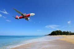 Το αεροπλάνο που προσγειώνεται στον αερολιμένα Phuket πέρα από την παραλία της Mai Khao Στοκ Φωτογραφίες