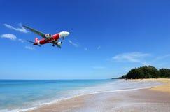Το αεροπλάνο που προσγειώνεται στον αερολιμένα Phuket πέρα από την παραλία της Mai Khao Στοκ Εικόνα