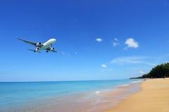 Το αεροπλάνο που προσγειώνεται στον αερολιμένα Phuket πέρα από την παραλία της Mai Khao Στοκ Εικόνες