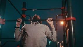 Το αθλητικό άτομο εκπαιδεύει στον οριζόντιο φραγμό στην κρύα νύχτα, επιλύει απόθεμα βίντεο