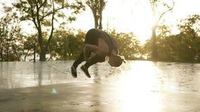 Το αθλητικό άτομο στα μαύρα περιστασιακά ενδύματα που εκτελεί τα κτυπήματα acrobatics και κάνει τούμπα υπαίθριος - stedycam σε αρ απόθεμα βίντεο