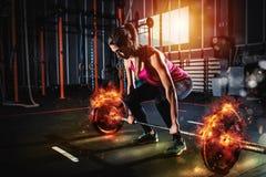 Το αθλητικό κορίτσι επιλύει στη γυμναστική με ένα φλογερό barbell Στοκ Εικόνα
