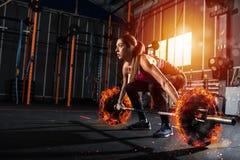 Το αθλητικό κορίτσι επιλύει στη γυμναστική με ένα φλογερό barbell Στοκ φωτογραφία με δικαίωμα ελεύθερης χρήσης