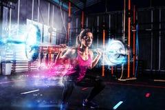 Το αθλητικό κορίτσι επιλύει στη γυμναστική με ένα barbell με τα μπλε ενεργειακά αποτελέσματα Στοκ φωτογραφία με δικαίωμα ελεύθερης χρήσης