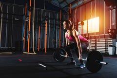 Το αθλητικό κορίτσι επιλύει στη γυμναστική με ένα barbell Στοκ εικόνες με δικαίωμα ελεύθερης χρήσης